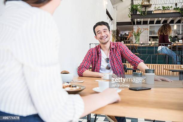 Young Asian man in cafe with coffee, smiling