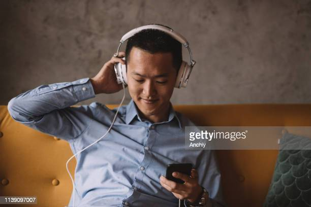 young asian man listening to music and relaxing in his office - listening stock pictures, royalty-free photos & images