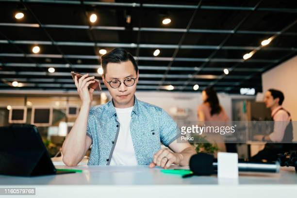 young asian man listening voice message in co-working space - speech recognition stock pictures, royalty-free photos & images