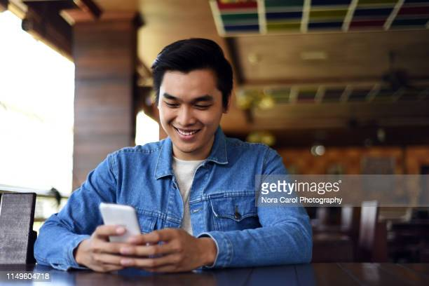 young asian man looking at the smart phone - kota kinabalu stock pictures, royalty-free photos & images