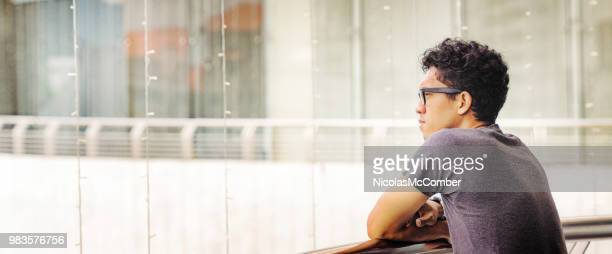 young asian man looking on balcony panoramic version - one mature man only stock pictures, royalty-free photos & images