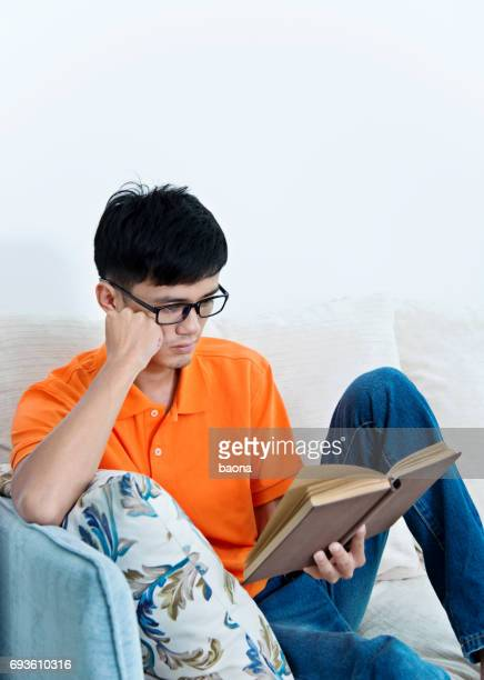 Young asian man reading a book at home