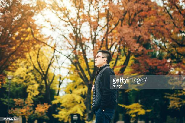 young asian man relaxing in autumn park and enjoying the scenics of red maple leaves - japan korea ストックフォトと画像