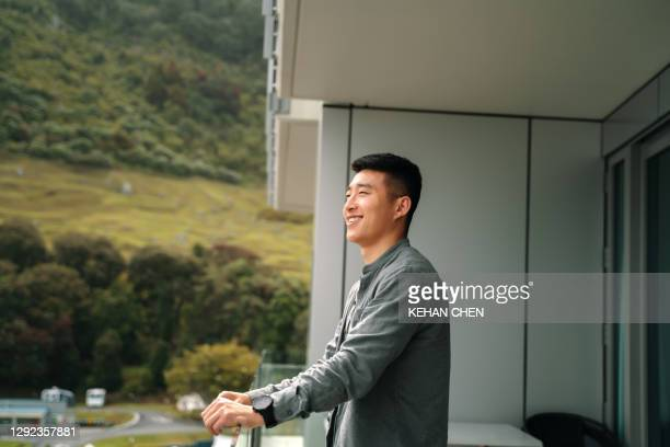 young asian man relaxing, take it easy in standing on hotel balcony - mid adult stock pictures, royalty-free photos & images