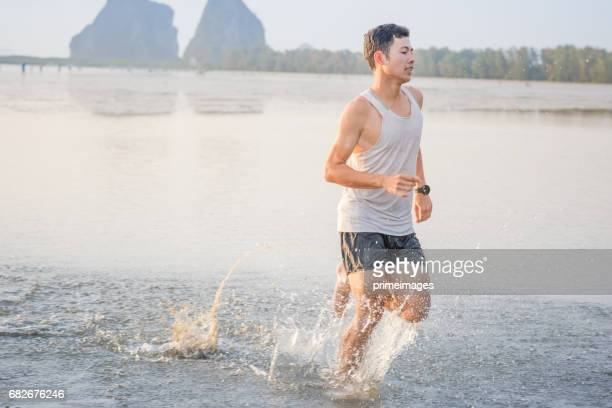 Young asian man running on beach with sunset in background