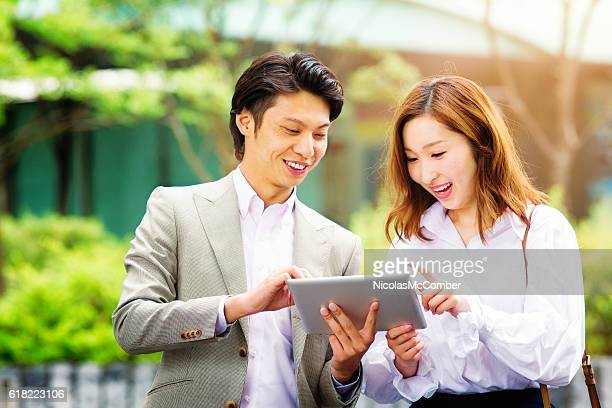 Young Asian man shares family photos on tablet