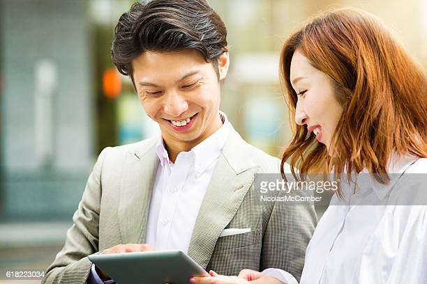 Young Asian man shares family photos with female friend