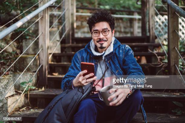 young asian man smiling joyfully at camera while using smartphone in country side - only men stock pictures, royalty-free photos & images