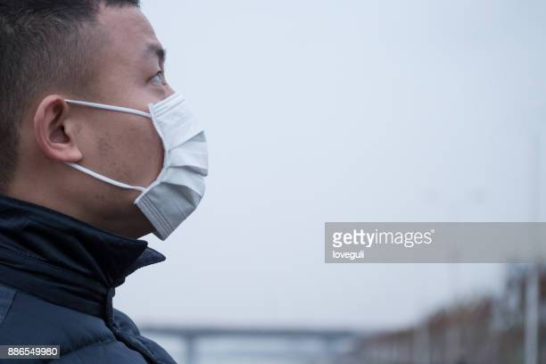 young asian man stands with white mask in foggy day