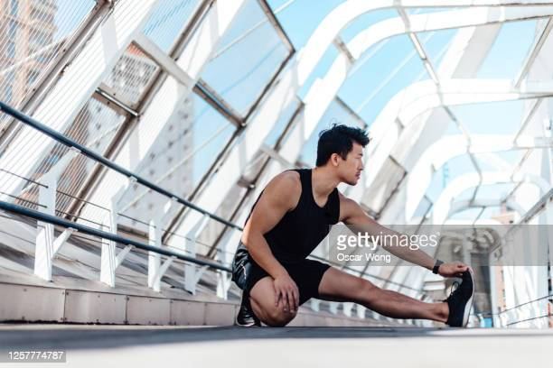 young asian man stretching his legs after workout - street style stock pictures, royalty-free photos & images