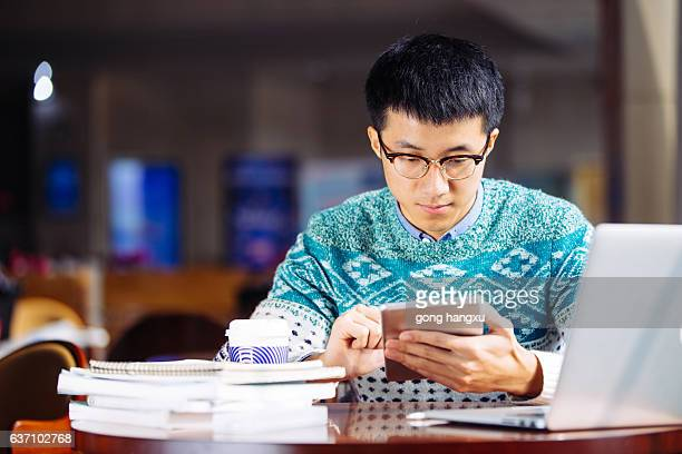young asian man student holds tablet