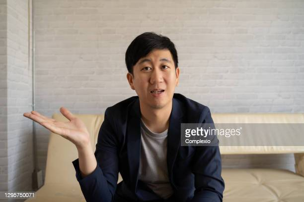 young asian man talking in video call with business colleagues at home. businessman having online video conference discussion in suit - webcam stock pictures, royalty-free photos & images