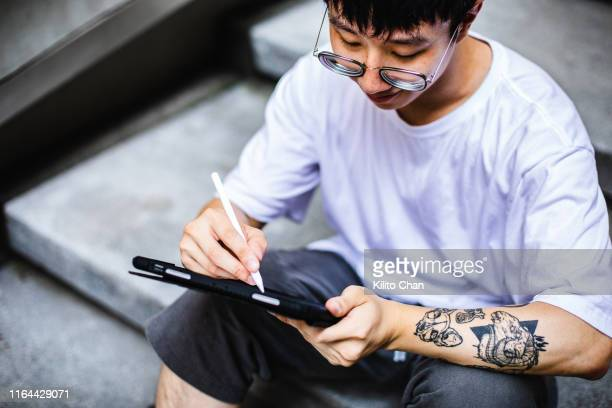 young asian man using digital devices on staircase - artist stock pictures, royalty-free photos & images