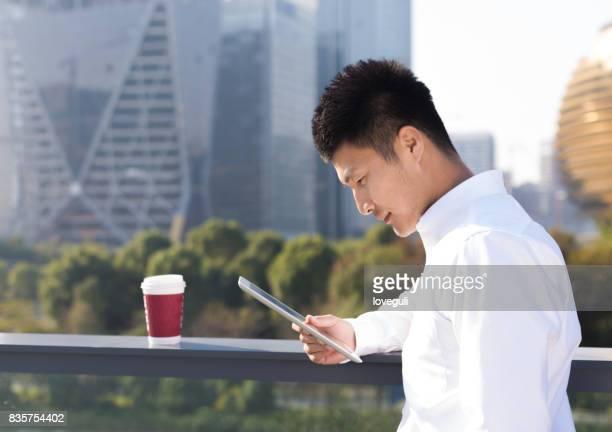 デジタル タブレットを使用して若いアジア男
