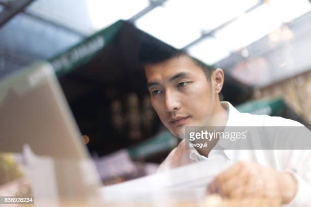 young asian man using laptop