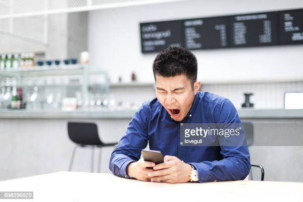 young asian man using mobile phone in modern cafe