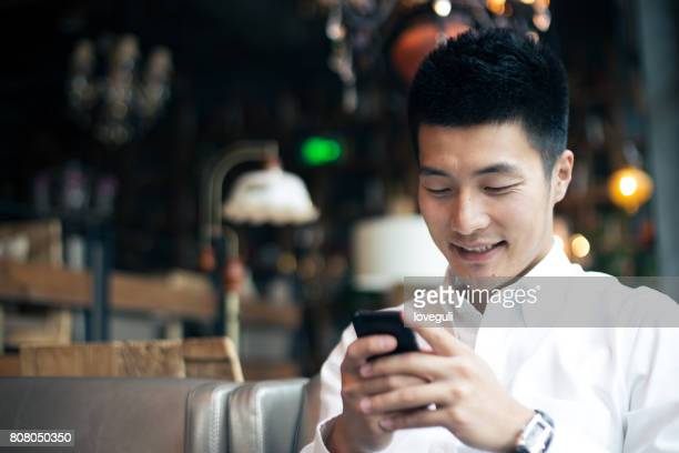 young asian man using mobile phone - handsome chinese men stock pictures, royalty-free photos & images