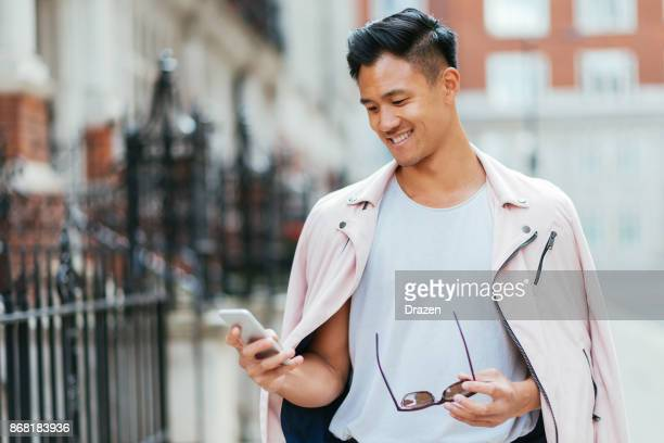 Young Asian man using smartphone for online messaging
