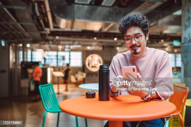 young asian man using smartphone while having drinks with a reusable bottle. - facebook stock pictures, royalty-free photos & images