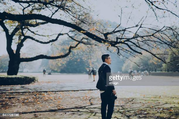 Young Asian man walking in the park in Autumn