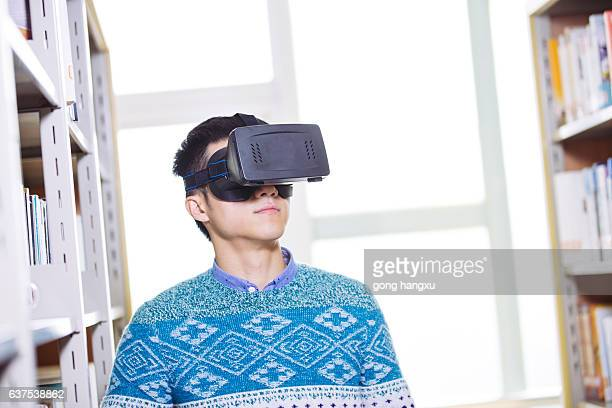 young asian man wearing VR in library