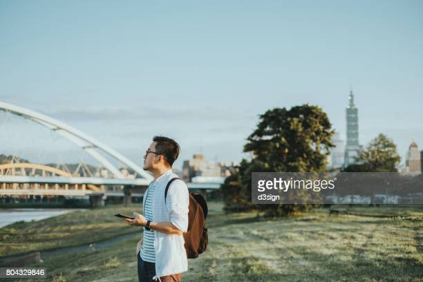 Young Asian man with backpack looking for direction with smartphone outdoor