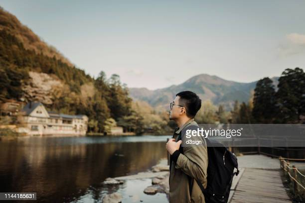 young asian man with backpack sightseeing at lake relaxing and enjoying the beautiful scenics - satoyama scenery stock pictures, royalty-free photos & images