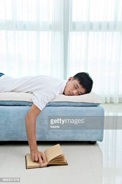 Junge asiatische Mann mit Buch eingeschlafen auf sofa
