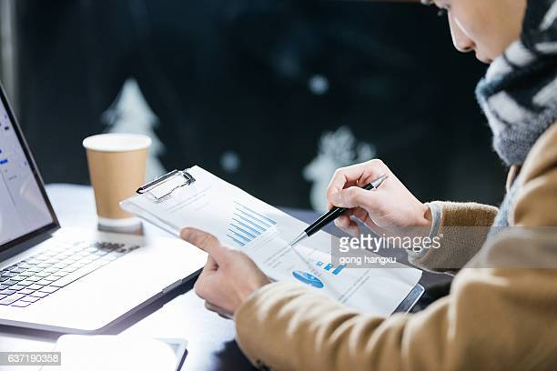 young asian man with laptop and clipboard in cafe