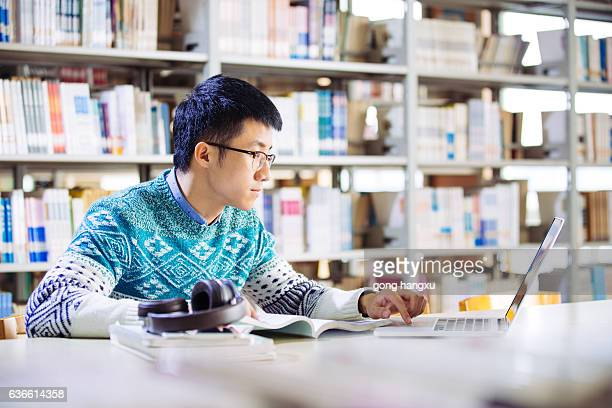 young asian man with laptop in library