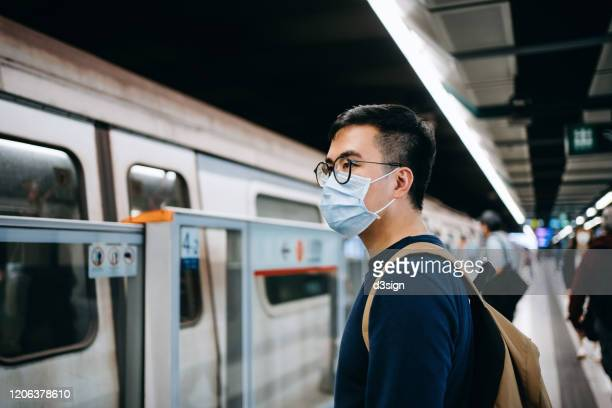 young asian man with protective face mask commuting in the city and waiting for subway in platform - coronavirus stock pictures, royalty-free photos & images