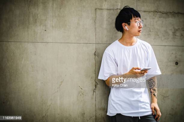 young asian man with sleeve tattoo using wireless electronic device - ブルートゥース ストックフォトと画像