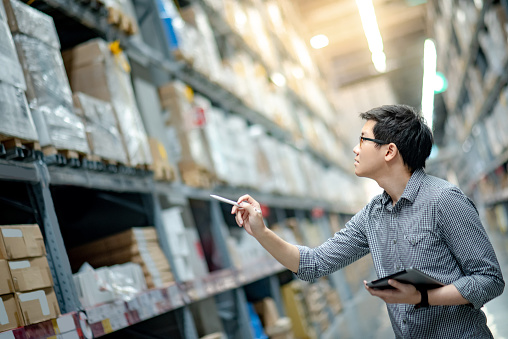 Young Asian man worker doing stocktaking of product in cardboard box on shelves in warehouse by using digital tablet and pen. Physical inventory count concept 1031295170