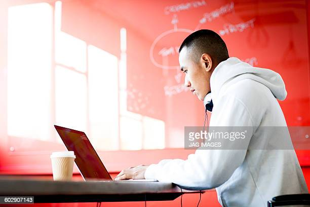 young asian man working on his laptop computer - red stock pictures, royalty-free photos & images
