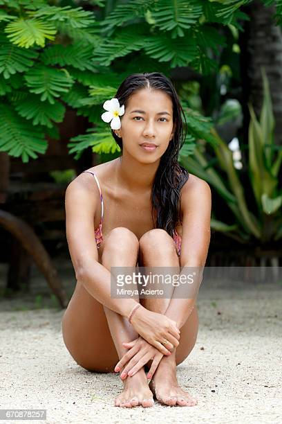 young asian model with flower in tropical setting - japanese swimsuit models stock photos and pictures