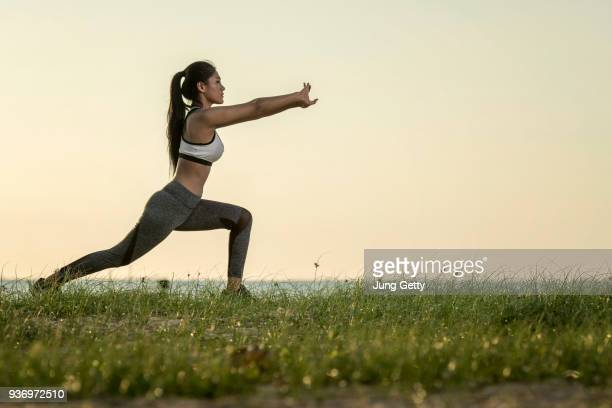 young asian models yoga. beautiful teenage girl in sports clothing training yoga position on the mat the beach during sunset time - yogi stock photos and pictures