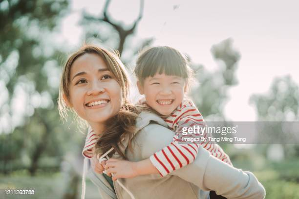 young asian mom carrying her daughter on back in park joyfully - asia stock pictures, royalty-free photos & images