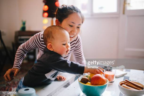 young asian mom giving food to her baby boy - snack stock pictures, royalty-free photos & images