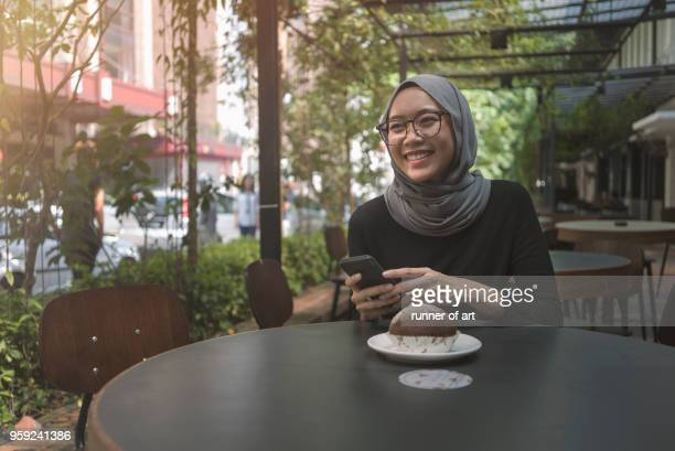 Young asian momen received a good news from her handphone