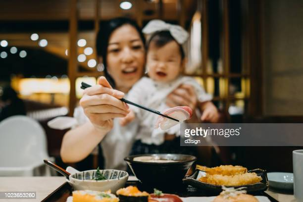Young Asian mother and baby girl enjoying fresh sushi set joyfully in a Japanese restaurant