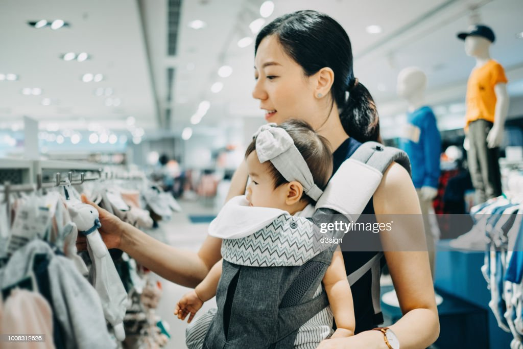 Young Asian mother and baby girl shopping and looking at soft toys in a shop : Stock Photo
