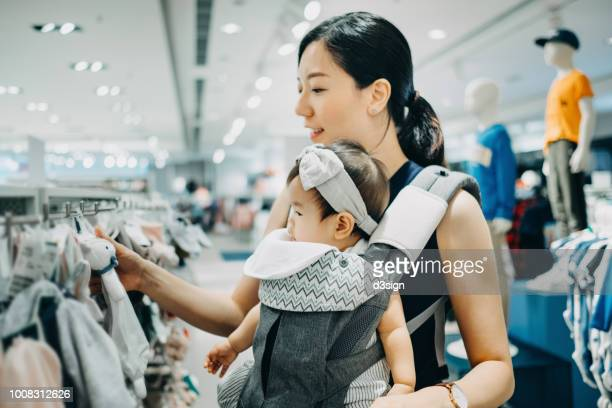 young asian mother and baby girl shopping and looking at soft toys in a shop - baby clothing stock pictures, royalty-free photos & images