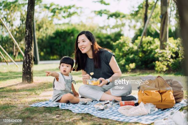 young asian mother and cute little daughter enjoying family bonding time having a picnic on a beautiful day in park - natural parkland stock pictures, royalty-free photos & images