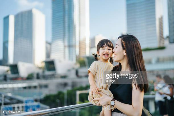 young asian mother and cute little daughter smiling joyfully over the urban terrace in downtown district against modern skyscrapers - prosperity stock pictures, royalty-free photos & images