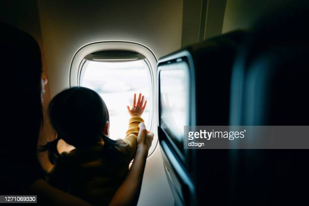 young asian mother and excited little daughter looking out through window in airplane while travelling on holiday - toddler at airport stock pictures, royalty-free photos & images