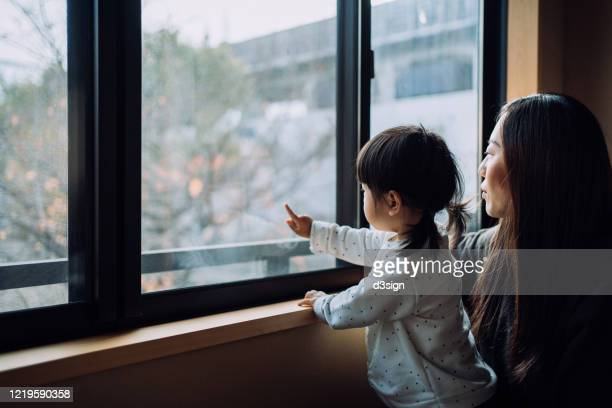 young asian mother and little daughter looking through window while on self isolation at home to prevent the spread of viruses due to the outbreak of covid-19 health crisis. hoping the epidemic of coronavirus will be ended soon - sadgirl stock pictures, royalty-free photos & images