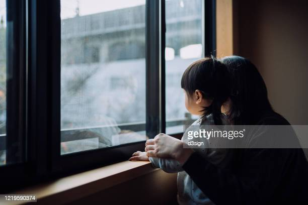 young asian mother and little daughter looking through window while on self isolation at home to prevent the spread of viruses due to the outbreak of covid-19 health crisis. hoping the epidemic of coronavirus will be ended soon - sad child stock pictures, royalty-free photos & images