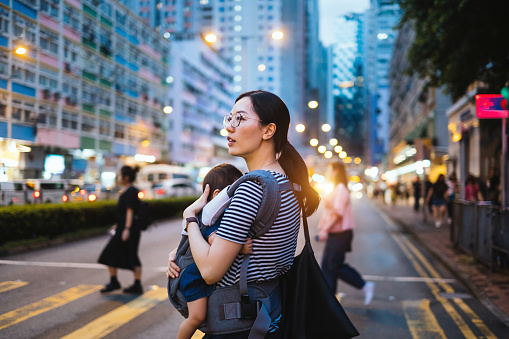 Young Asian mother carrying baby girl crossing road in urban city street at sunset - gettyimageskorea