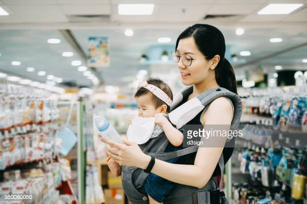 Young Asian mother carrying cute baby girl shopping for baby product in a shopping mall and is looking at a variety of baby bottles