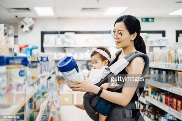 Young Asian mother carrying cute baby girl shopping for baby product in a shopping mall and is looking at a variety of baby formula